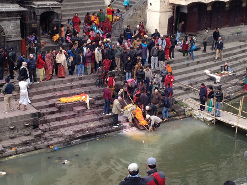 Family members washing the body of a deceased loved on with chai, before setting the body on fire.